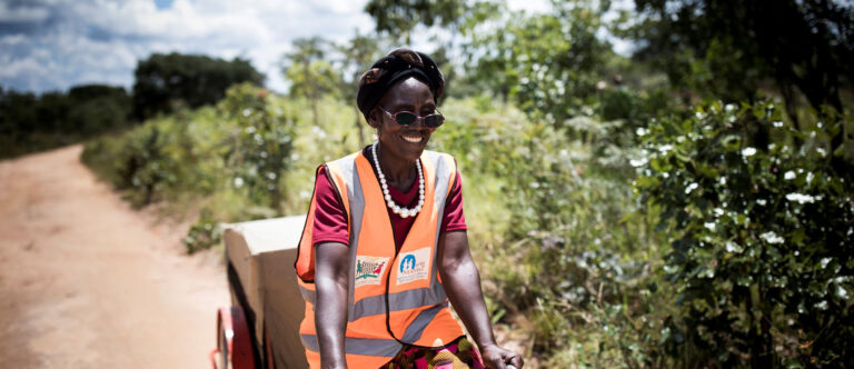 woman on bike delivering vaccine in Zambia